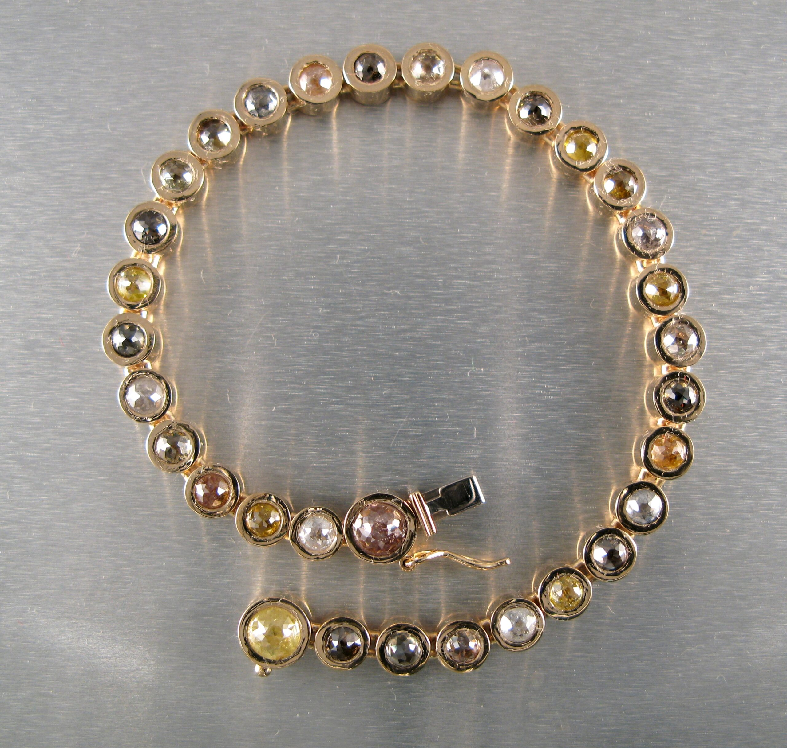 Ledat armband i guld med rosenslipade naturfärgade diamanter.